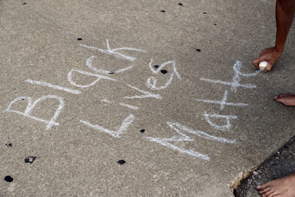 """A protester writes, """"Black Lives Matter,"""" on the ground with a chalk as protesters gather, Friday, Sept. 15, 2017, in downtown St. Louis, after a judge found a white former St. Louis police officer, Jason Stockley, not guilty of first-degree murder in the death of a black man, Anthony Lamar Smith, who was fatally shot following a high-speed chase in 2011. (AP Photo/Jeff Roberson)"""