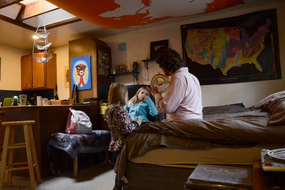 In this Tuesday, Nov. 28, 20017 photo, TC Bell sits with his two daughters Dagny, 8 and Emma, 4 before they get dressed for school, at their home in Denver. Bell's daughters are recipients of the Children's Health Insurance Program or CHIP, which is a program that provides low-cost coverage to families who earn too much to qualify for Medicaid. Arizona, California, Colorado, Minnesota, Ohio, Oregon and the District of Columbia are among the first expected to exhaust their CHIP allotments. (AP Photo/Tatiana Flowers)