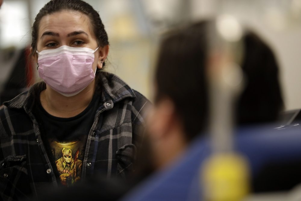 In this Jan. 10, 2018 photo, Torrey Jewett looks on as her roommate Donnie Cardenas recovers from the flu at the Palomar Medical Center in Escondido, Calif. Cardenas, a San Diego County resident, said he was battling a heavy cough for days before a spike his temperature sent him into the emergency room. (Gregory Bull/AP)