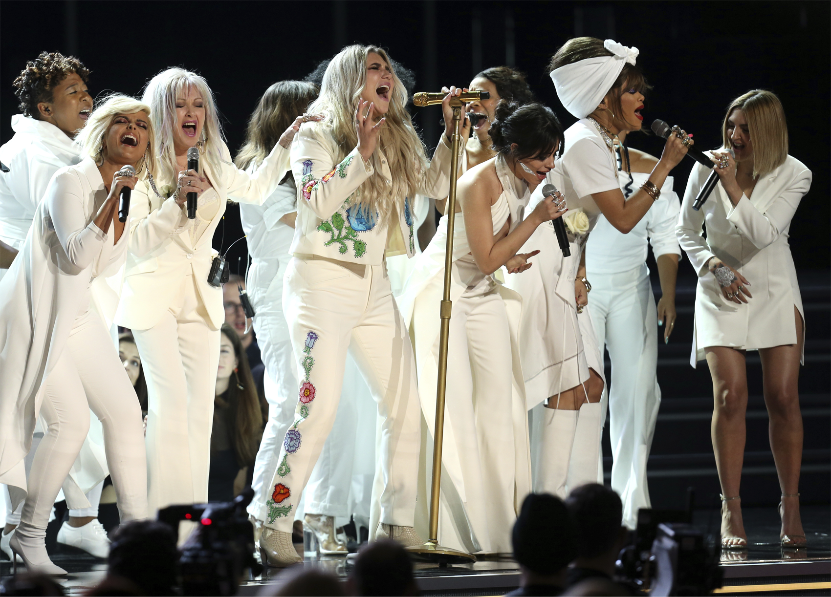 """Kesha, center, performs """"Praying"""" as, from left, Bebe Rexha, Cyndi Lauper, Camila Cabello, Andra Day and Julia Michaels provide back up vocals at the 60th annual Grammy Awards. (Matt Sayles/AP)"""