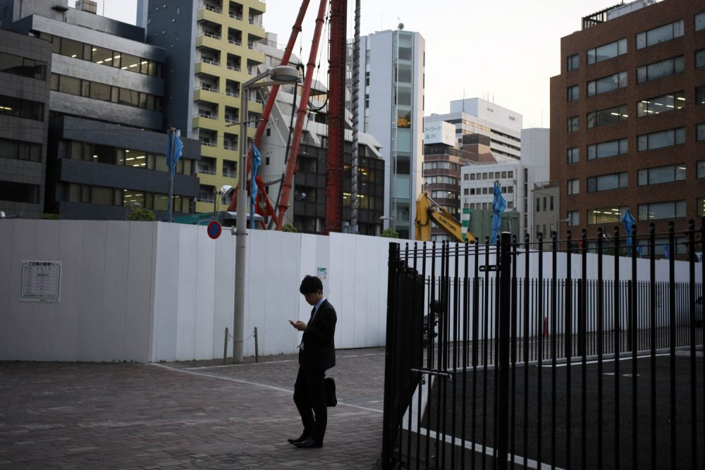FILE - In this May 8, 2013 file photo, a man looks at his mobile phone near a construction site in Tokyo.  (AP Photo/Greg Baker, File)