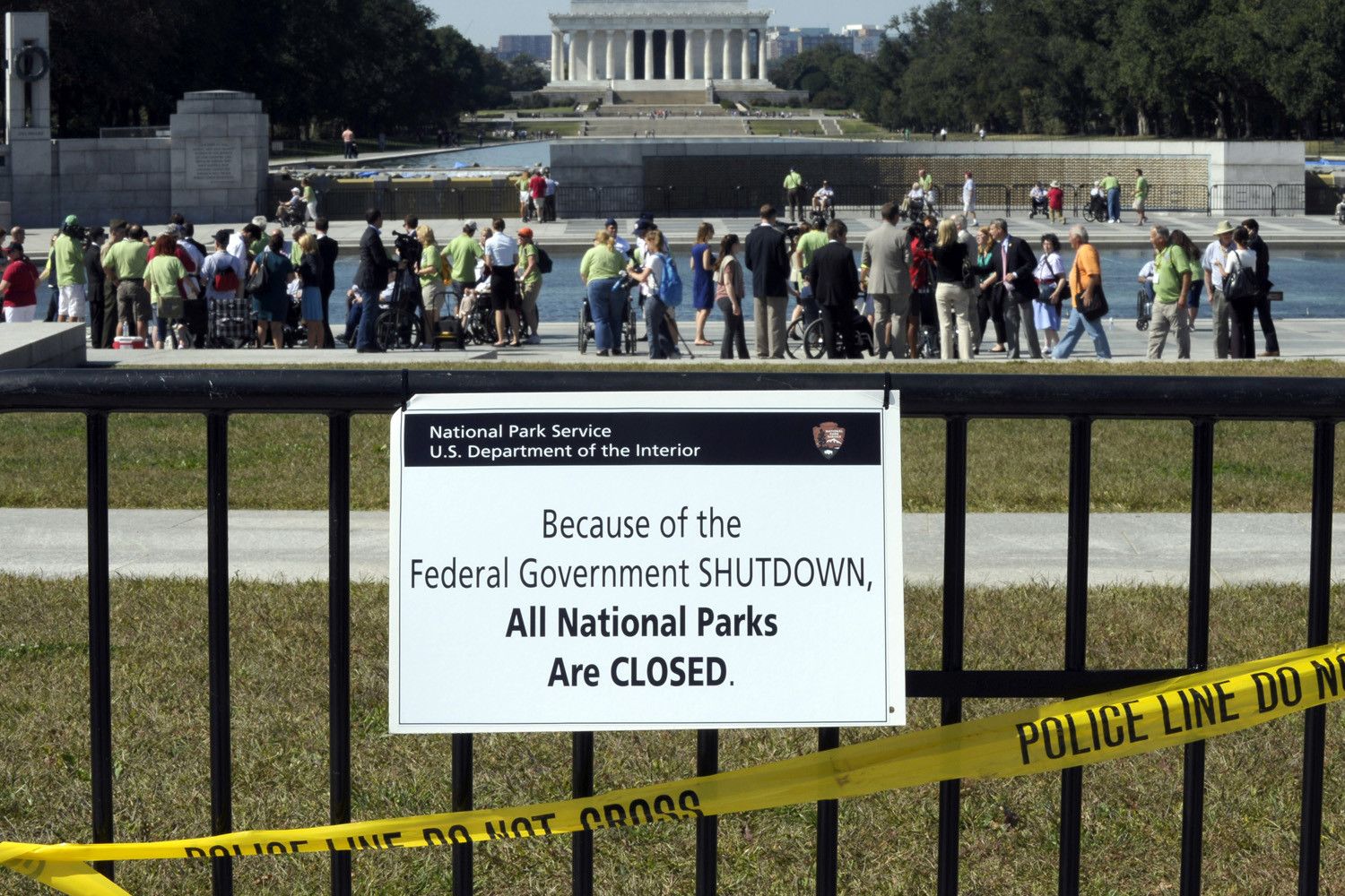 In this Oct. 2, 2013 file photo, despite signs stating that the national parks are closed, people visit the World War II Memorial in Washington. (Susan Walsh/AP)