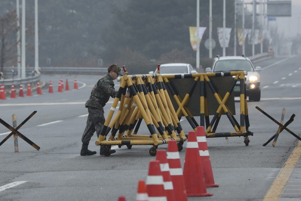 A South Korean soldier adjusts barricade before South Korea's delegation vehicle's arriving at Unification Bridge, which leads to the Panmunjom in the Demilitarized Zone in Paju, South Korea, Monday, Jan. 15, 2018. Officials from the two Koreas met Monday to work out details about North Korea's plan to send an art troupe to the South during next month's Winter Olympics, as the rivals tried to follow up on the North's recent agreement to cooperate in the Games in a conciliatory gesture following months of nuclear tensions. (AP Photo/Lee Jin-man)