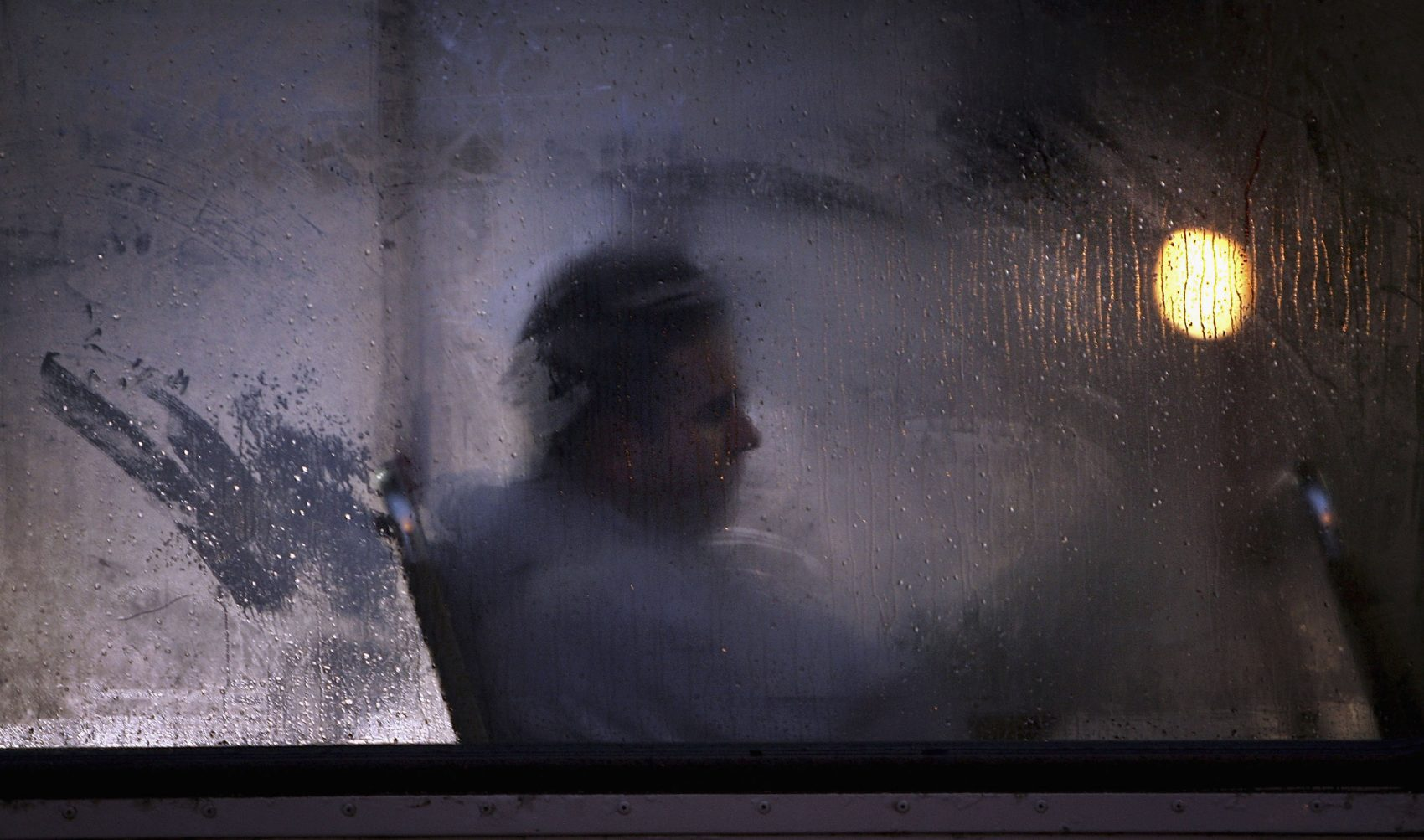 A man makes his way home from work on a bus as darkness falls in Glasgow, Scotland. (Christopher Furlong/Getty Images)