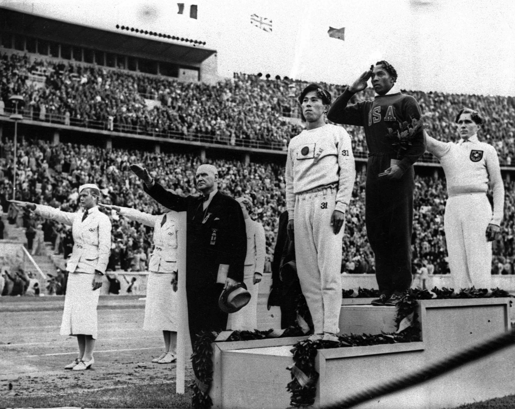 In this Aug. 11, 1936 file photo, Olympic broad jump medalists salute during the medals ceremony at the Summer Olympics in Berlin. From left on podium are: bronze medalist Jajima of Japan, gold medalist Jesse Owens of the United States and silver medalist Lutz Long of Germany. (AP Photo)