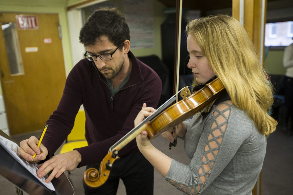 Boston String Academy instructor Tony Morales makes a few adjustments to the music Eliza Youngman will be playing. (Jesse Costa/WBUR)