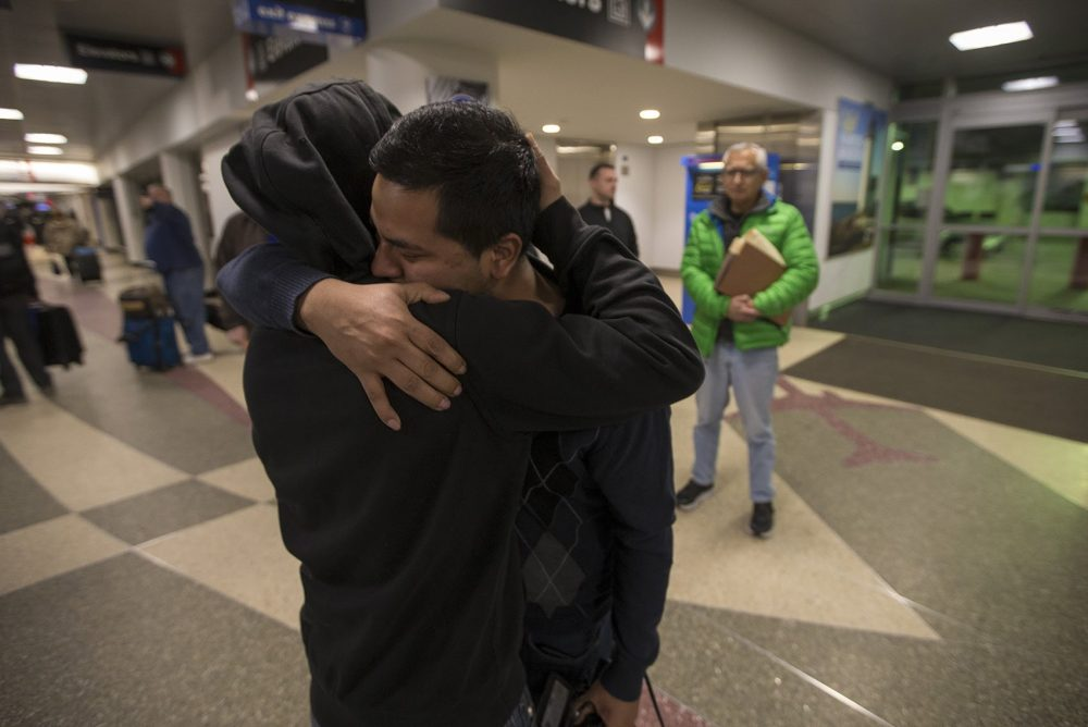Isidro Macario, right, hugs his younger brother Erwin goodbye before being escorted by ICE officers to the boarding gate at Logan Airport. (Jesse Costa/WBUR)