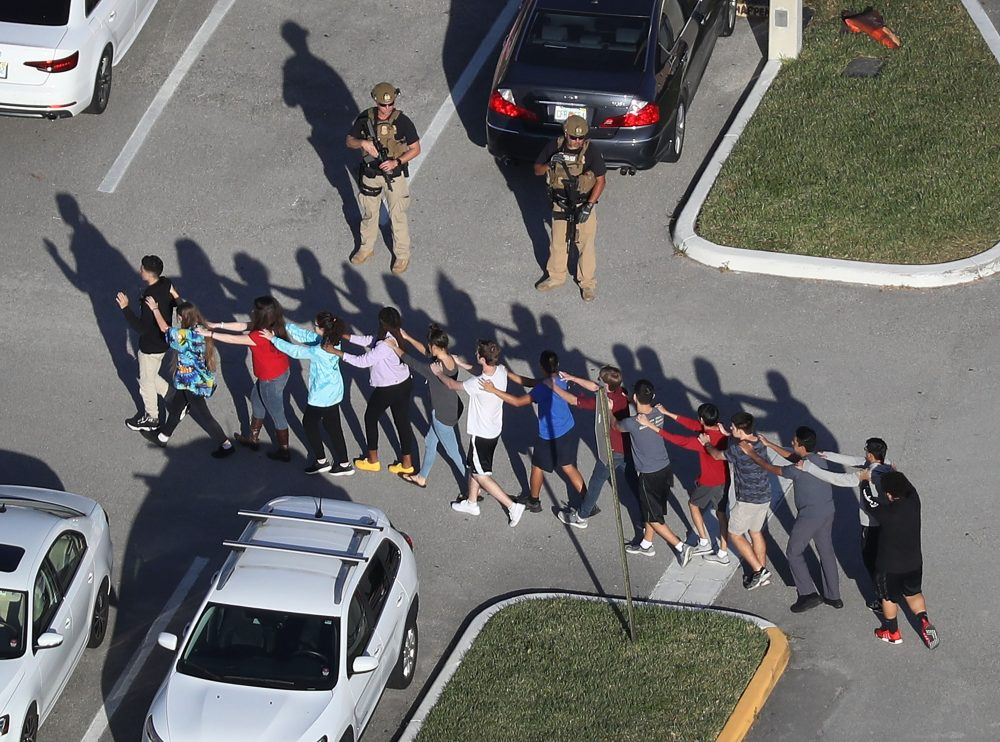 "People are brought out of the Marjory Stoneman Douglas High School after a shooting on Feb. 14, 2018 in Parkland, Fla. President Trump's reference to the school resource officer who remained outside during the shooting as a ""coward"" sparked a national conversation about cowardice. (Joe Raedle/Getty Images)"
