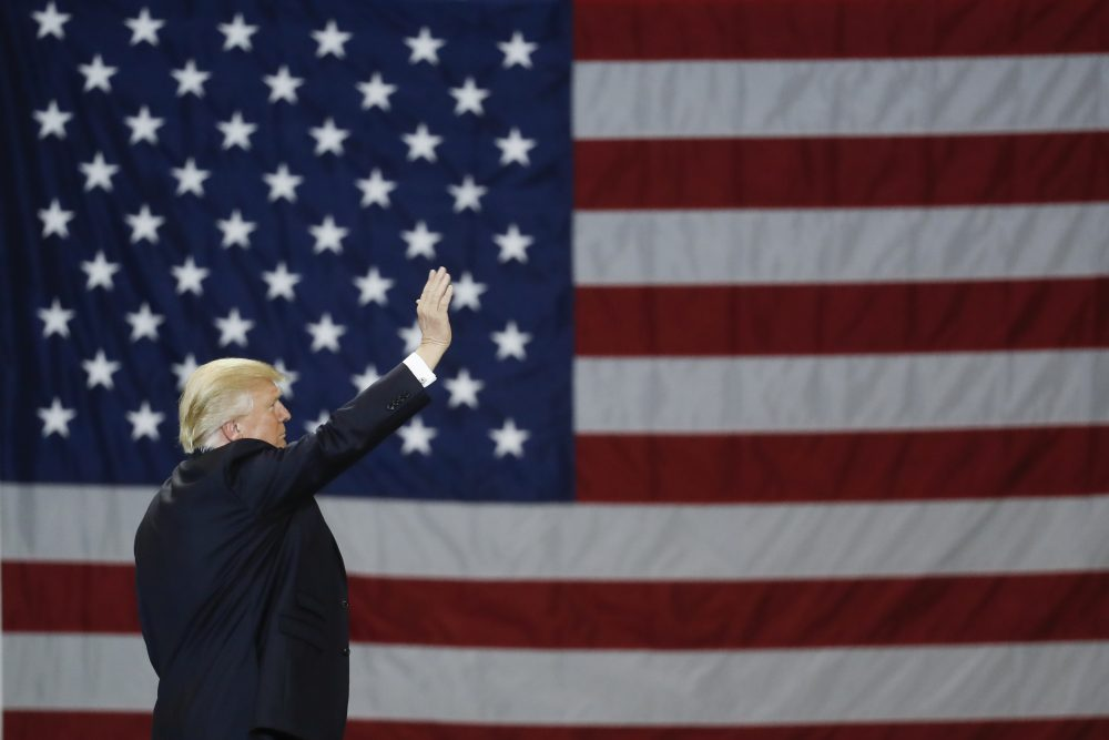 President Donald Trump waves in front of an American flag, March 20, 2017, in Louisville, Ky. (John Minchillo/AP)