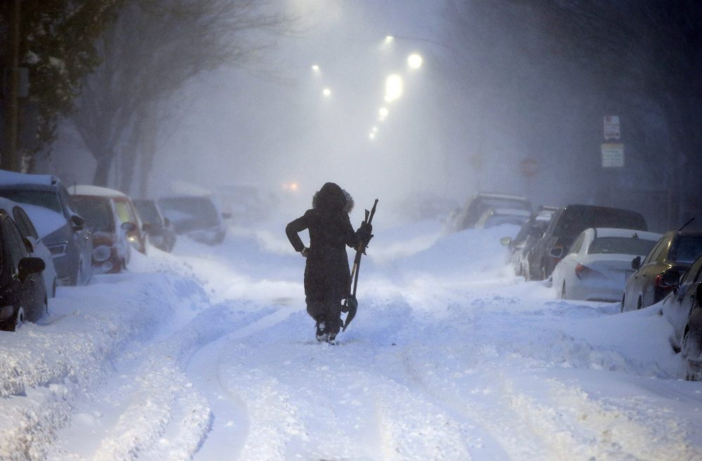 A woman walks down snow-covered Maverick Street in the East Boston neighborhood of Boston, Thursday, Jan. 4, 2018, as a huge winter storm roared up the East Coast with hurricane-force winds, heavy snow and coastal flooding. (Michael Dwyer/AP)