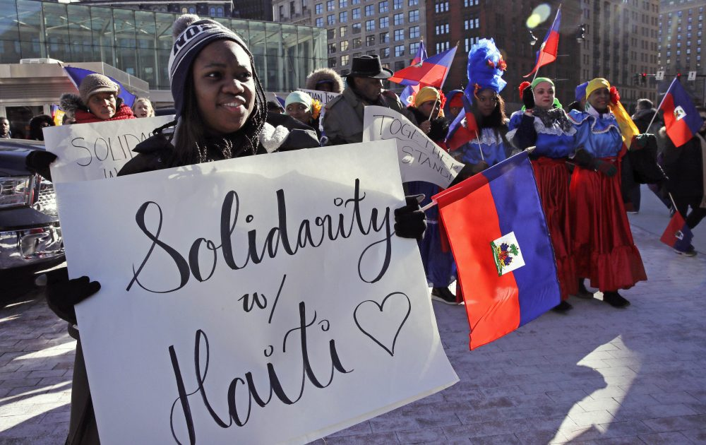 Haitian activists and immigrants protest on Boston City Hall Plaza on Jan. 26. Haitian community leaders complained last week that the Trump administration's delays in re-registering those living in the U.S. legally through the Temporary Protected Status program would lead to job losses, travel problems and other issues for Haitians. (Charles Krupa/AP)