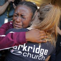 Marla Eveillard, 14, cries as she hugs friends before the start of a vigil at the Parkland Baptist Church, for the victims of the Marjory Stoneman Douglas High School shooting, which happened Wednesday, in Parkland, Fla., Thursday, Feb. 15, 2018. (Gerald Herbert/AP)