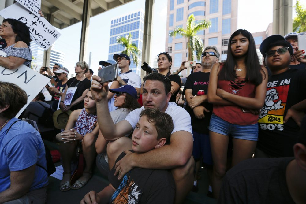 Louis Reinstein, embraces his son, Daniel, 10, during a protest against guns on the steps of the Broward County federal courthouse in Fort Lauderdale, Fla., on Feb. 17. (Brynn Anderson/AP)