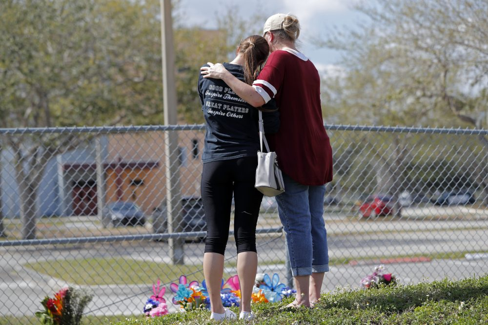 Hadley Sorensen, 16, a student at Marjory Stoneman Douglas High School, is comforted by her mother Stacy Sorensen at a makeshift memorial outside the school in Parkland, Fla., Sunday, Feb. 18, 2018, where 17 people were killed in a mass shooting. (Gerald Herbert/AP)