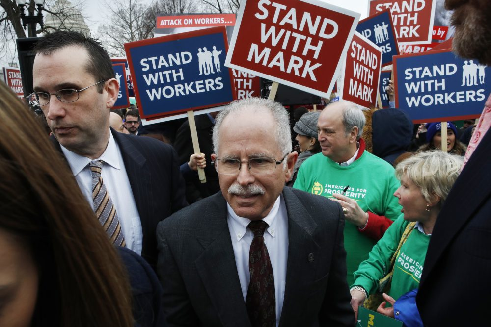 Illinois government employee Mark Janus, center, turns after thanking supporters outside the Supreme Court, Monday, Feb. 26, 2018, in Washington. The Supreme Court takes up a challenge Monday in a case that could deal a painful financial blow to organized labor. The court is considering a challenge to an Illinois law that allows unions representing government employees to collect fees from workers who choose not to join. (AP Photo/Jacquelyn Martin)