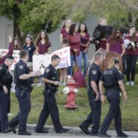 Police escort students arriving at Marjory Stoneman Douglas High School in Parkland, Fla., Wednesday, Feb. 28, 2018, on their first day back at the school since a former student opened fire there with an assault rifle, killing 17 people. (Terry Renna/AP)