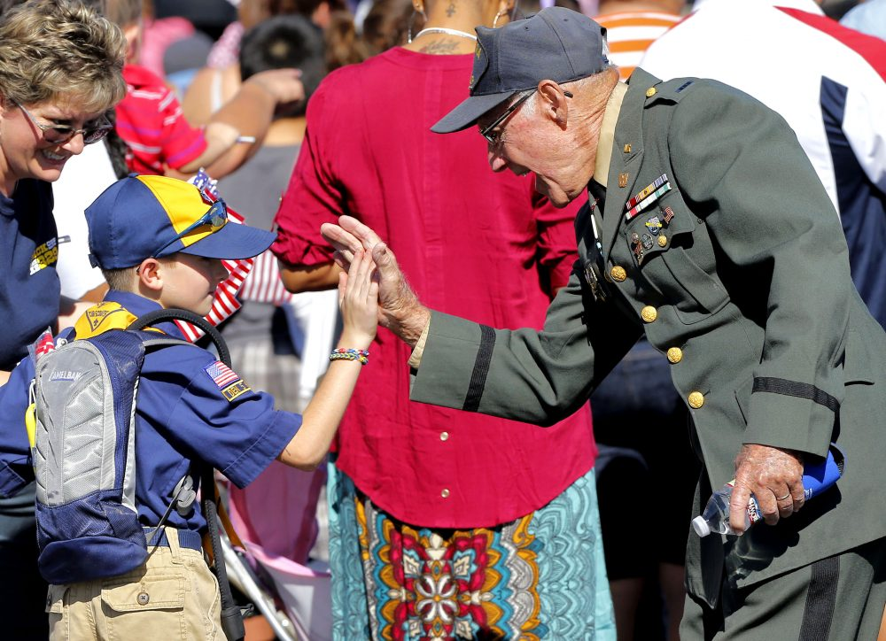 Cub Scout Carter Chase, 7, high fives WWII U.S. Army veteran Oliver Babbitts during a Veteran's Day parade, Monday, Nov. 11, 2013, in downtown Phoenix. (Matt York/AP)