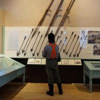 A man looks at harpoons used by whalers to kill the mammals in the water and bring them aboard their vessels at sea on display at the New Bedford Whaling Museum. (John Bender/RIPR)