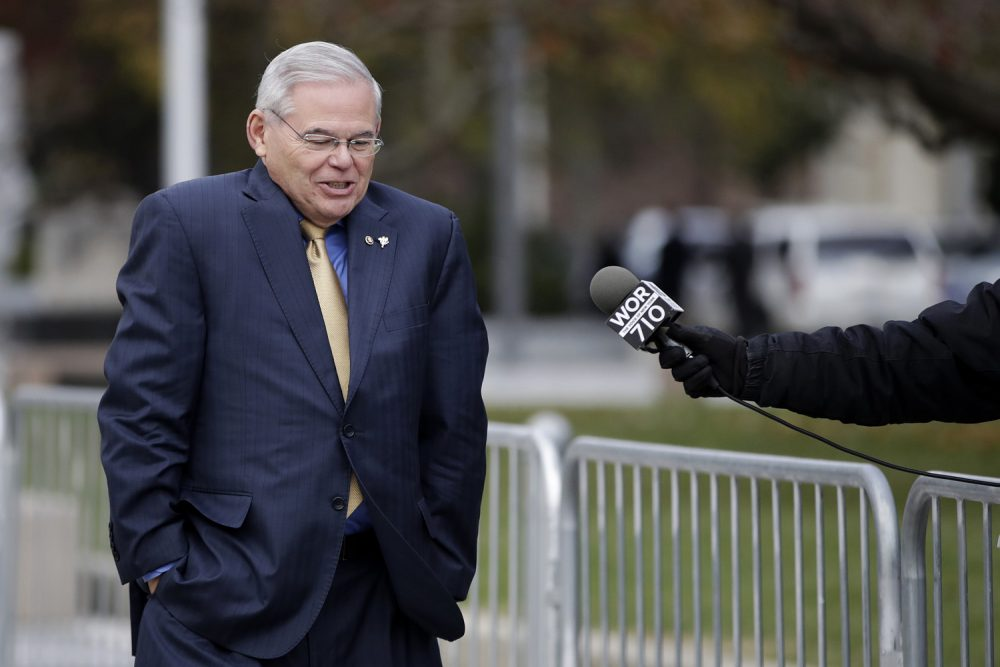 U.S. Sen. Bob Menendez, center, shrugs as a reporter asks him questions while leaving the Martin Luther King Jr. Federal Courthouse after stopping in to appear on his corruption trial, Tuesday, Nov. 14, 2017, in Newark, N.J. Jury deliberations in the bribery trial of Menendez continued Tuesday. (AP Photo/Julio Cortez)
