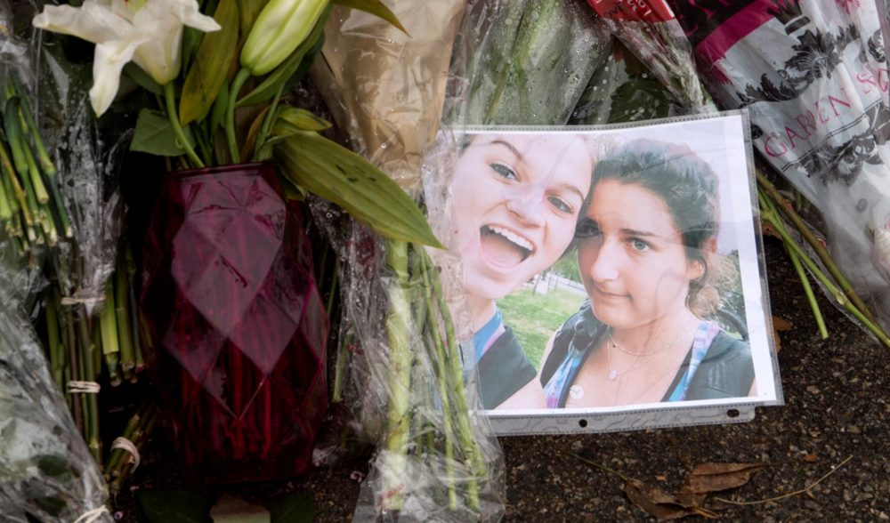 A photograph of Adrienne Garrido, 17, and Talia Newfield, 16, at the roadside memorial. (Max Larkin/WBUR)
