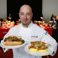 Aramark Senior Executive at U.S. Bank Stadium Chef James Mehne holds signature sandwiches he created for Super Bowl LII celebrating hometown flavors of the Philadelphia Eagles, left, and New England Patriots, right, at the Super Bowl menu preview in Minneapolis. (Andy Clayton-King/AP for Aramark)