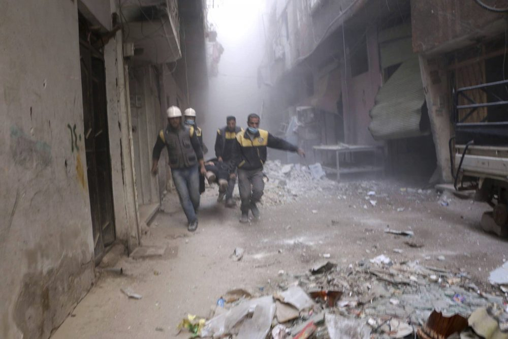 This photo released on Friday, Feb. 23, 2018 provided by the Syrian Civil Defense group known as the White Helmets, shows members of the Syrian Civil Defense group carrying a man who was wounded during airstrikes and shelling by Syrian government forces, in Ghouta, a suburb of Damascus, Syria. Syrian government warplanes supported by Russia continued their relentless bombardment of the rebel-controlled eastern suburbs of Damascus for a sixth day Friday, killing five people, opposition activists and a war monitor reported. The death toll from the past week climbed to more than 400. (Syrian Civil Defense White Helmets via AP)