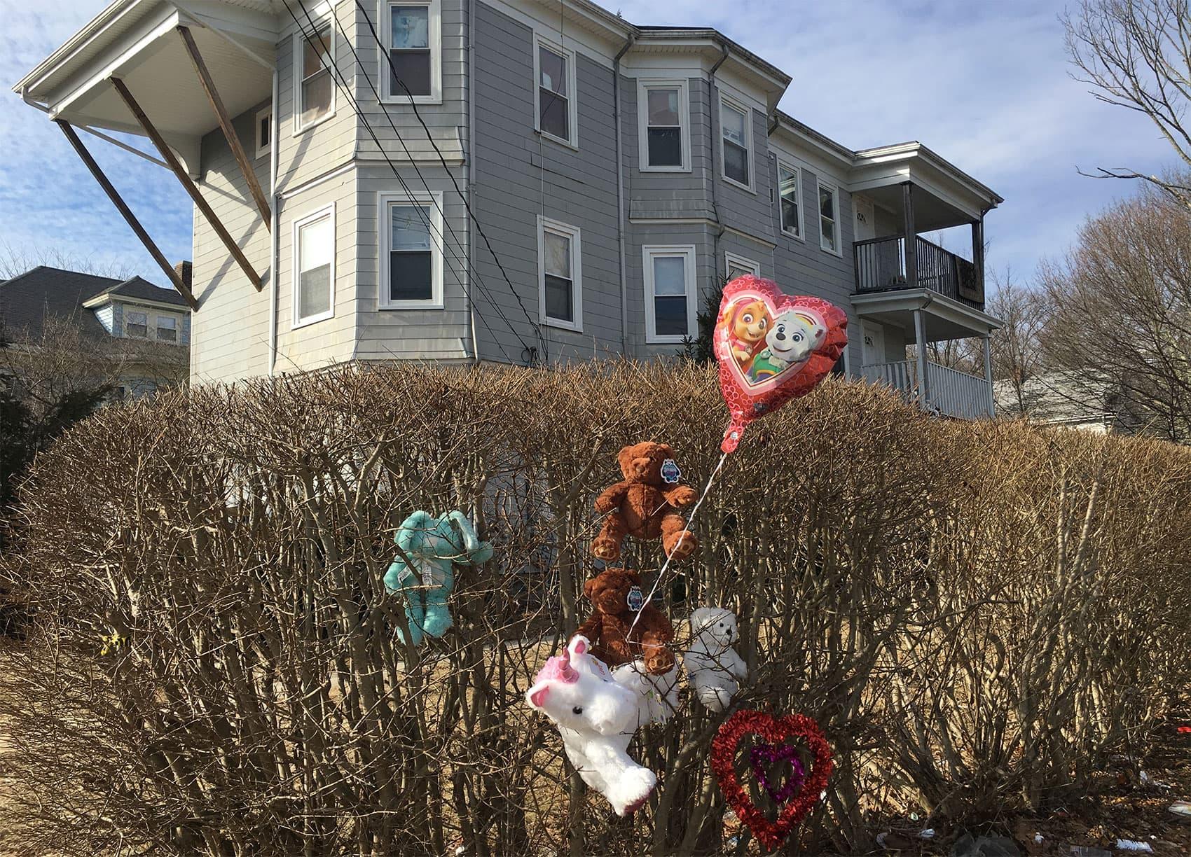 Balloons and stuffed animals are left outside 247 Prospect St., in Brockton, where the slain children were found. (Bruce Gellerman/WBUR)