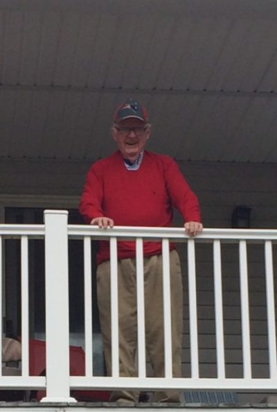 The author's father watching a parade from the porch of his condominium.