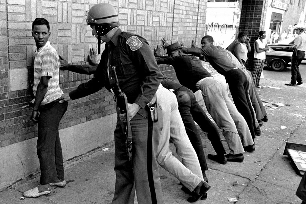 FILE - In this July 24, 1967 file photo, a Michigan State police officer searches a youth on Detroit's 12th Street where looting was still in progress after the previous day's rioting. The last surviving member of the Kerner Commission says he remains haunted that the panel's recommendations on US race relation and poverty were never adopted, but he is hopeful they will be one day. Former U.S. Sen. Fred Harris says 50 years after working on a report to examine the causes of the late 1960s race riots he strongly feels that poverty and structural racism still enflames racial tensions even as the United States becomes more diverse. (AP Photo/File)