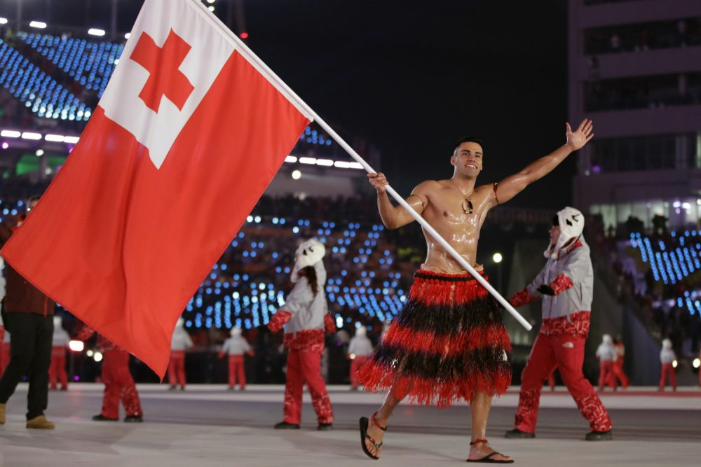 Pita Taufatofua carries the flag of Tonga during the opening ceremony of the 2018 Winter Olympics in Pyeongchang, South Korea, Friday, Feb. 9, 2018. (AP Photo/Vadim Ghirda)