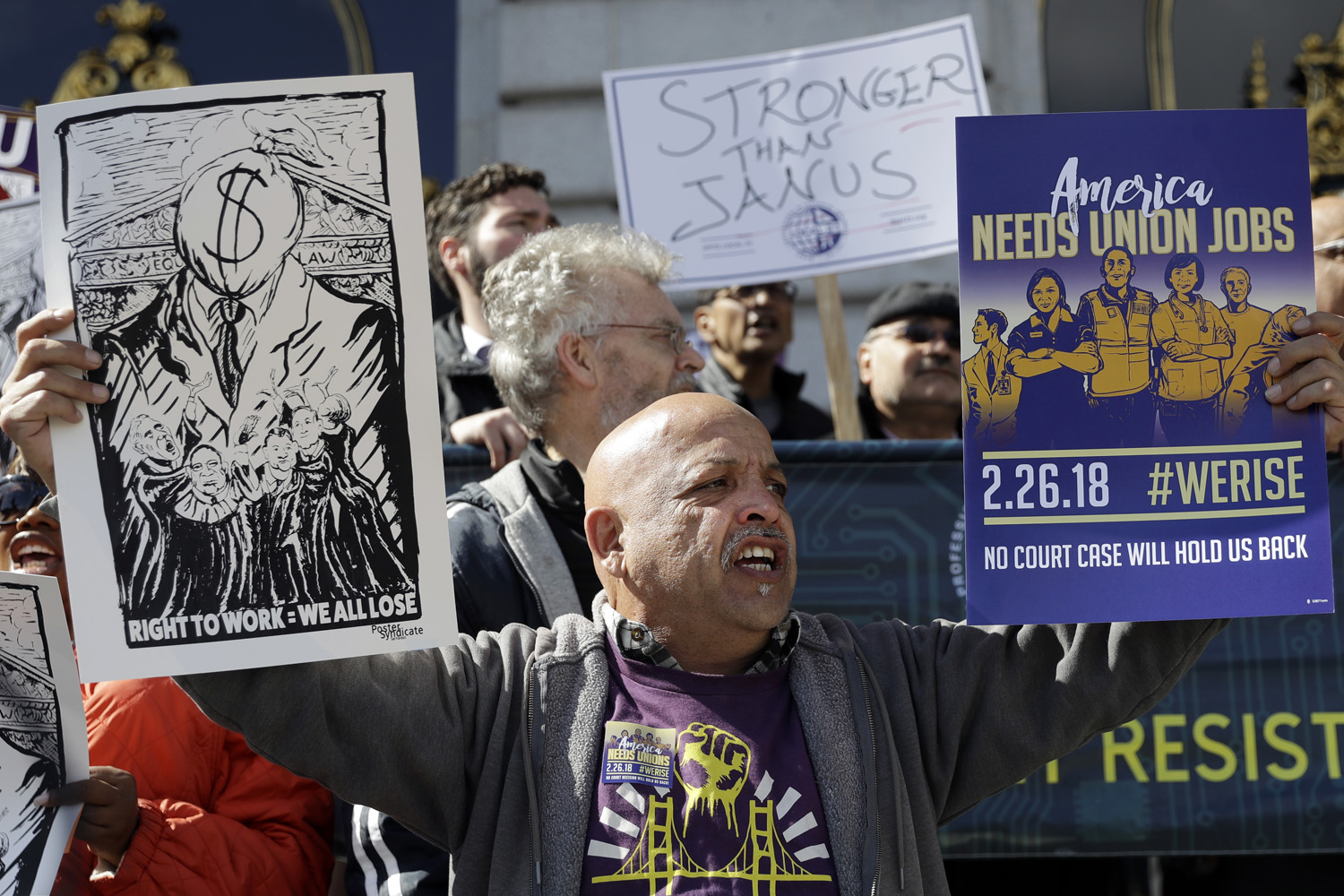 """A demonstrator holds pro-union signs during a demonstration involving various labor union groups Monday, Feb. 26, 2018, in San Francisco. The Supreme Court is divided in a major organized labor case over """"fair share"""" fees that nonmembers pay to help cover the costs of contract negotiations. (AP Photo/Marcio Jose Sanchez)"""