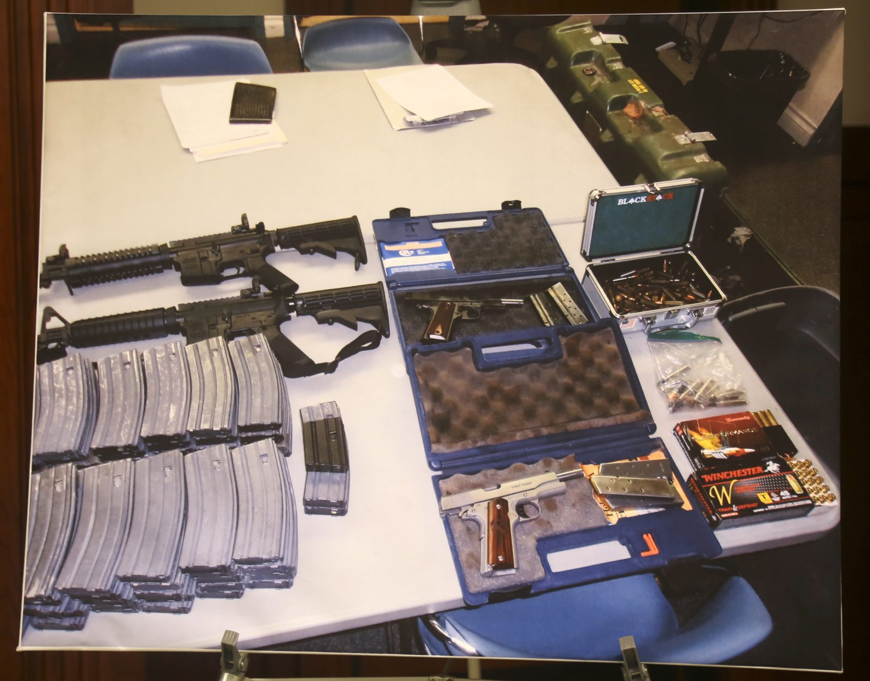 """A confiscated cache of weapons is displayed at a news conference in Los Angeles on Feb. 21. Authorities say they've thwarted a student's plot for a mass shooting at a Southern California high school. Authorities say a security guard at El Camino High School in Whittier overhead a """"disgruntled student"""" threaten to open fire on the school on Friday, just two days after 17 people were gunned down at a Florida high school. Deputies discovered """"multiple guns and ammunition"""" after searching the student's home. (Mike Balsamo/AP)"""