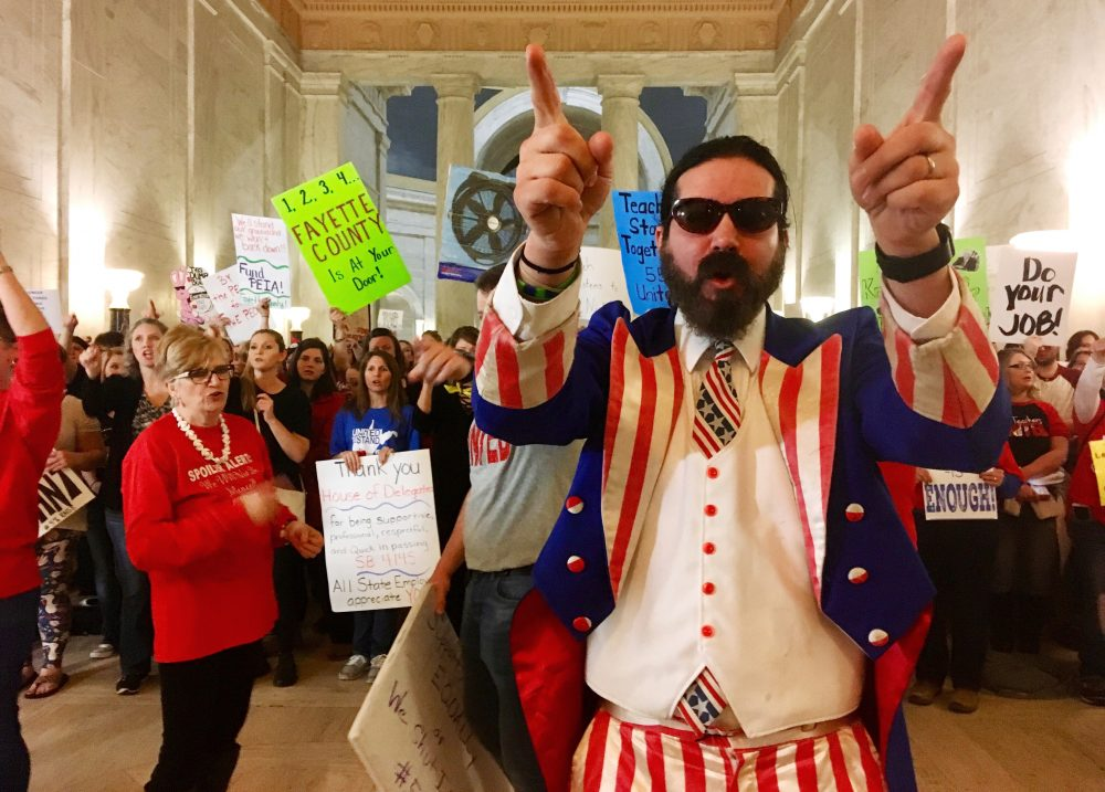 Parry Casto, a fifth grade teacher at the Explorer Academy in Huntington, W.Va., dressed in an Uncle Sam costume leads hundreds of teachers in chants outside the state Senate chambers at the Capitol in Charleston, W.Va., Thursday, March 1, 2018. Teachers were awaiting a Senate vote on a proposed 5 percent pay increase for them. (John Raby/AP)