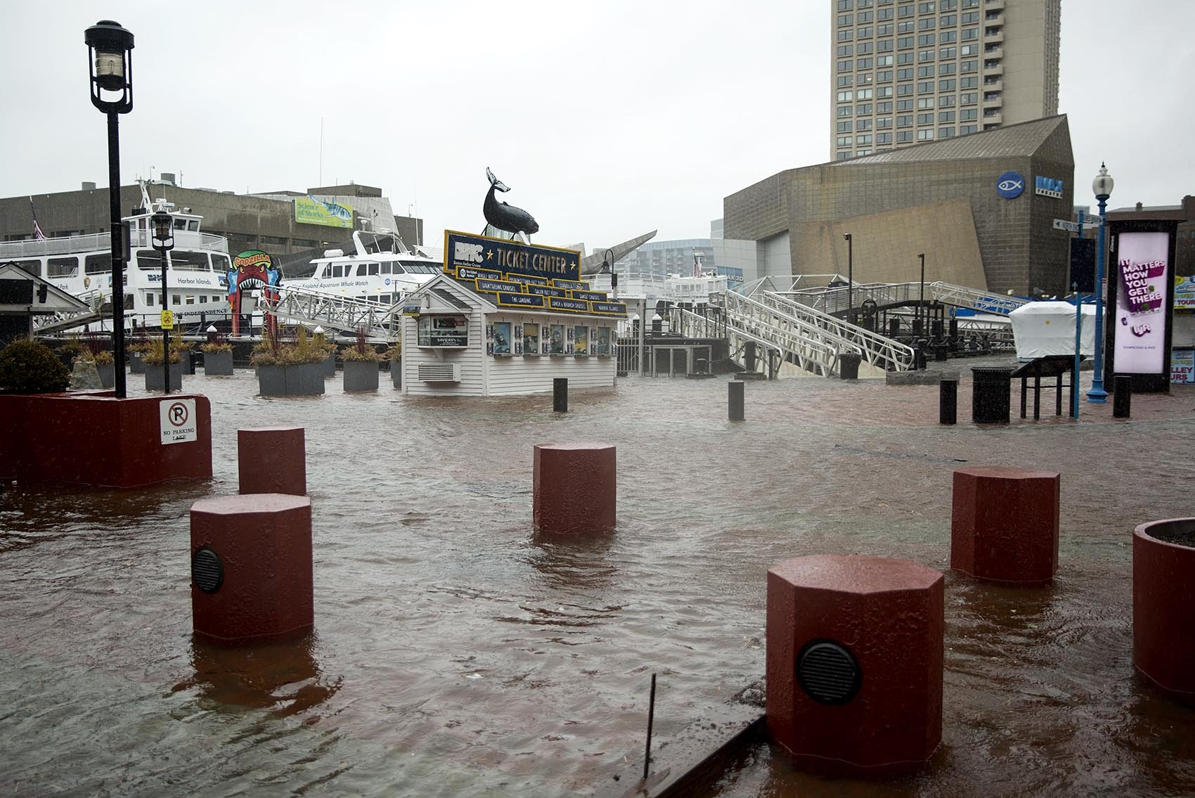 The Boston Harbor Cruises ticket office stands completely surrounded by water as high tide floods Long Wharf. (Robin Lubbock/WBUR)