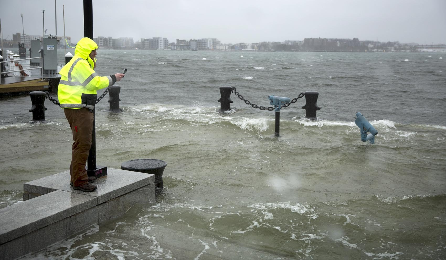 A man takes photographs as floodwaters surge at Boston's Long Wharf in 2018. (Robin Lubbock/WBUR)