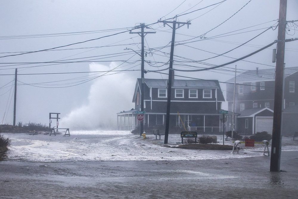 A wave crashes high above a house on Turner Road in Scituate on Friday. (Jesse Costa/WBUR)