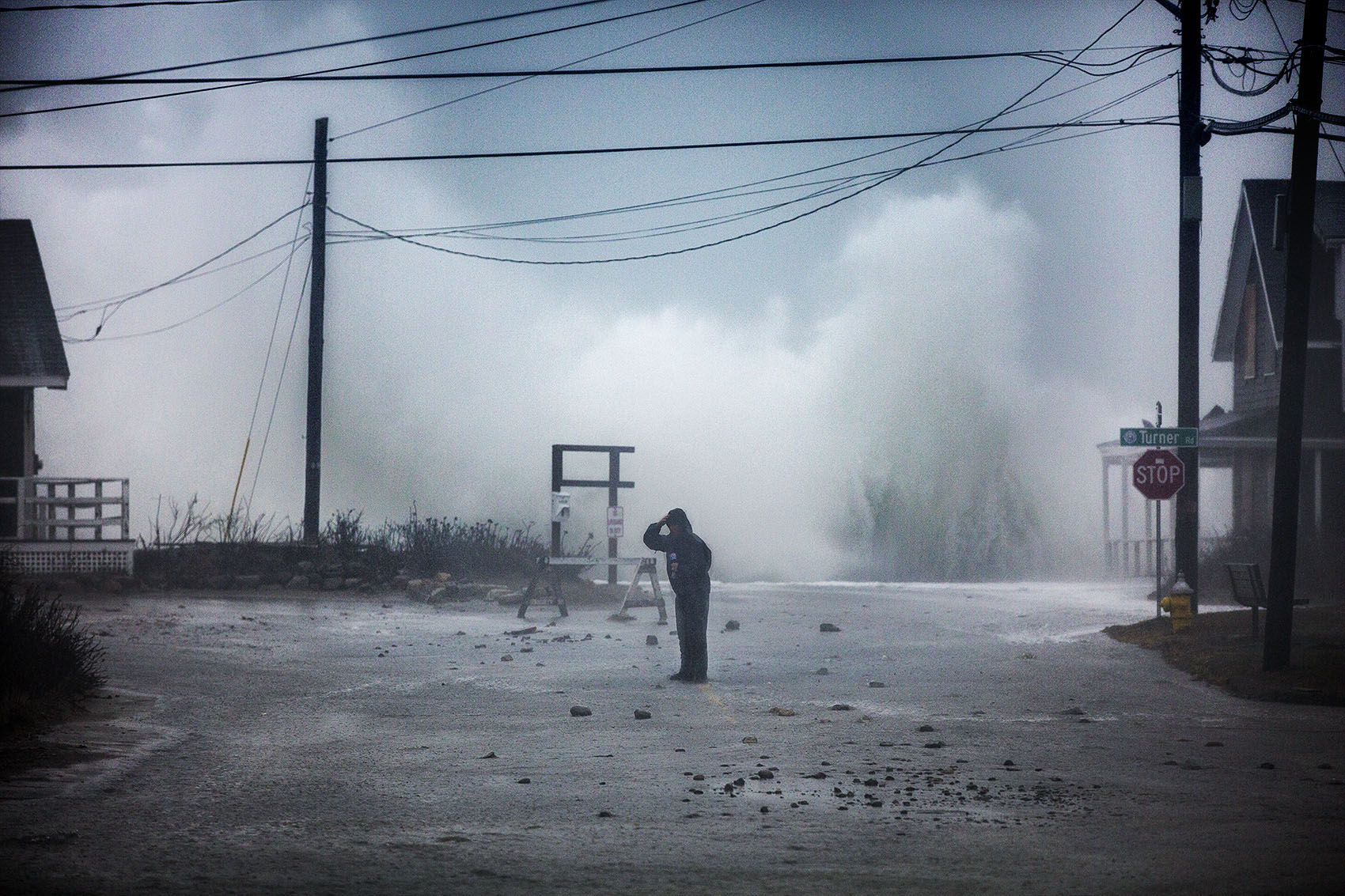 A TV news broadcaster stands in the middle of Jericho Road at Cedar Point in Scituate while waves crash on the seawall at high tide during the nor'easter on March 2. (Jesse Costa/WBUR)