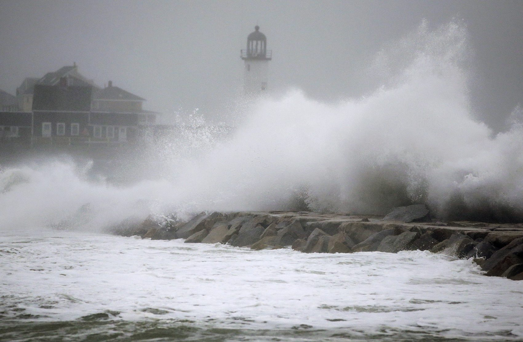 Waves crash against a seawall near the Scituate Lighthouse on Friday in Scituate. (Steven Senne/AP)