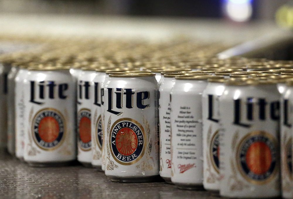 In this March 11, 2015 photo, newly filled and sealed cans of Miller Lite beer move along on a conveyor belt, at the MillerCoors Brewery, in Golden, Colo. (Brennan Linsley/AP)