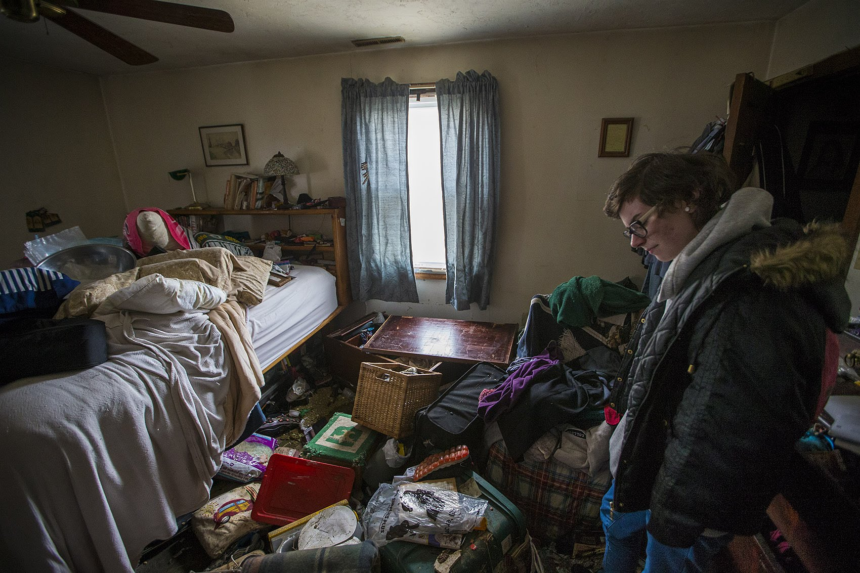 Taylor Fenton bows her head, looking at the damage in one of the family bedrooms in her home in Quincy caused by the nor'easter on Friday. (Jesse Costa/WBUR)