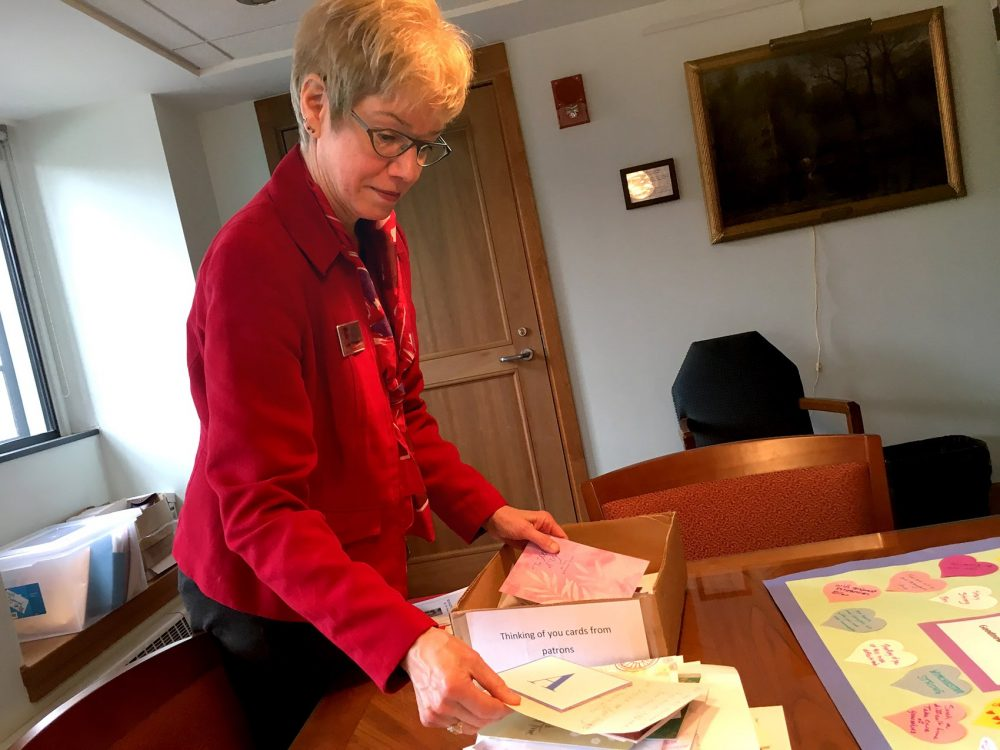 Ann Wirtanen, Director of Winchester Public Library, holds the letters that have come from community members and libraries across the country. (Yasmin Amer/WBUR)