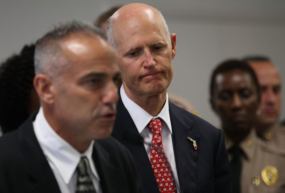 Florida Gov. Rick Scott listens as Andy Pollack, who lost his daughter Meadow Pollack, 18, during the mass shooting at Marjory Stoneman Douglas High School, speaks during a press conference at Miami-Dade police headquarters on Feb. 27, 2018 in Doral, Fla. (Joe Raedle/Getty Images)