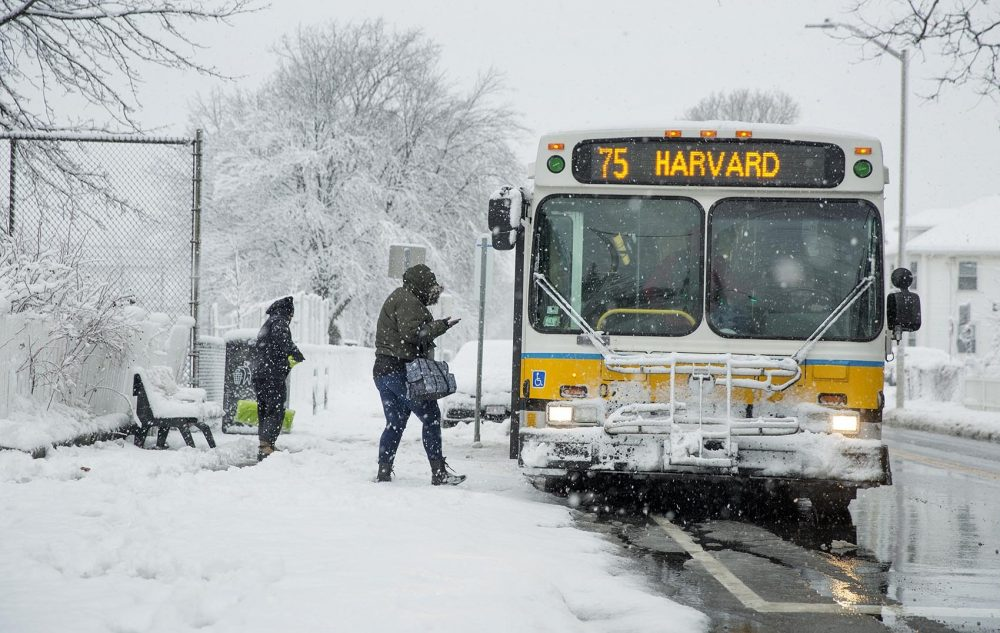 Bundled up against the snow, a woman boards a bus during the morning commute in Cambridge.(Robin Lubbock/WBUR)