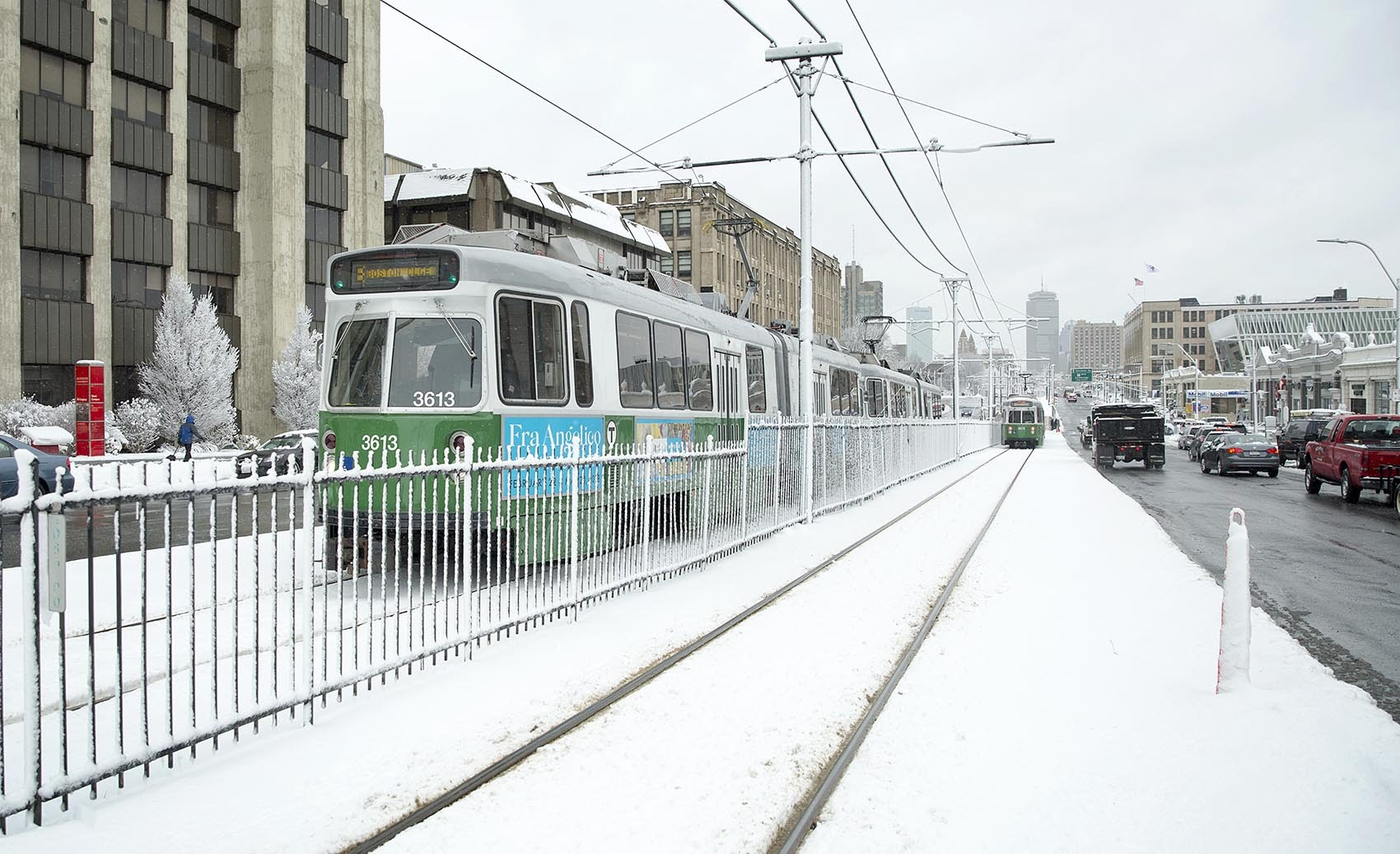 MBTA Green Line trains run along snow-covered lines in Boston after overnight snow. (Robin Lubbock/WBUR)