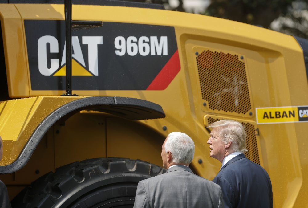 "President Trump and Vice President Mike Pence stop to looks at a Caterpillar truck, manufactured in Illinois, on the South Lawn of the White House in Washington, Monday, July 17, 2017, during a ""Made in America,"" product showcase featuring items created in each of the U.S. 50 states. (Pablo Martinez Monsivais/AP)"