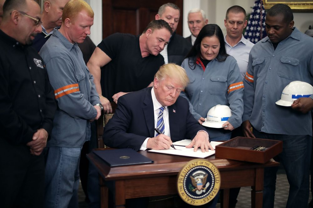 Surrounded by steel and aluminum workers, President Trump (center) signs a proclamation on steel imports during a ceremony in the Roosevelt Room at the White House on March 8, 2018 in Washington, D.C. (Chip Somodevilla/Getty Images)