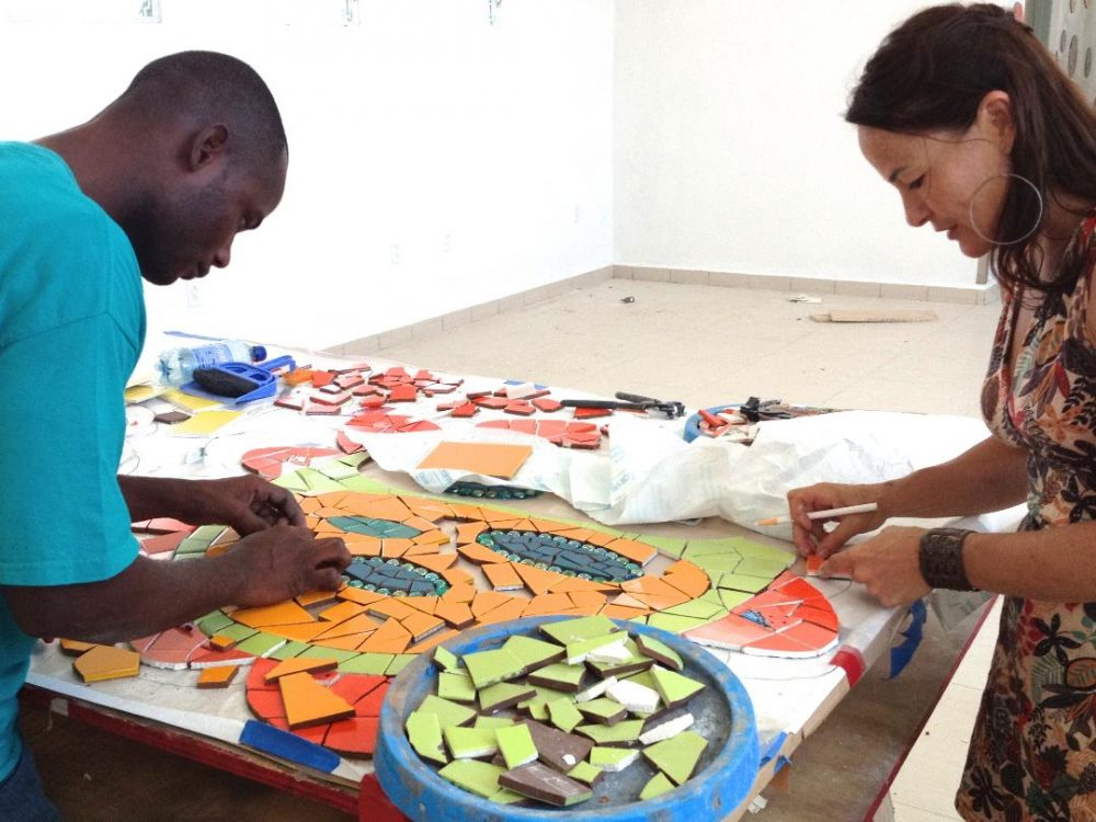 Artist Laurel True works with trainee Mario Jeudi on mosaics for a hospital in Mirebalais, Haiti. (Courtesy Laurel True)