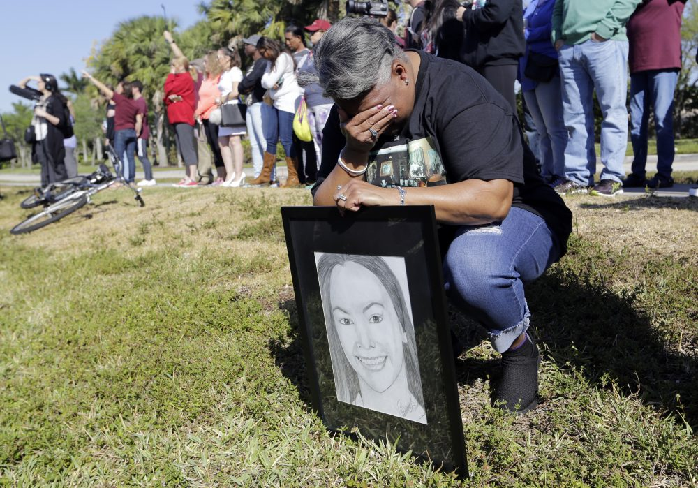 Pat Gibson holds a drawing of Meadow Pollack, a victim of the Marjory Stoneman Douglas High School shooting, as she kneels outside of the school as part of a nationwide protest against gun violence on Wednesday in Parkland, Fla. (Lynne Sladky/AP)
