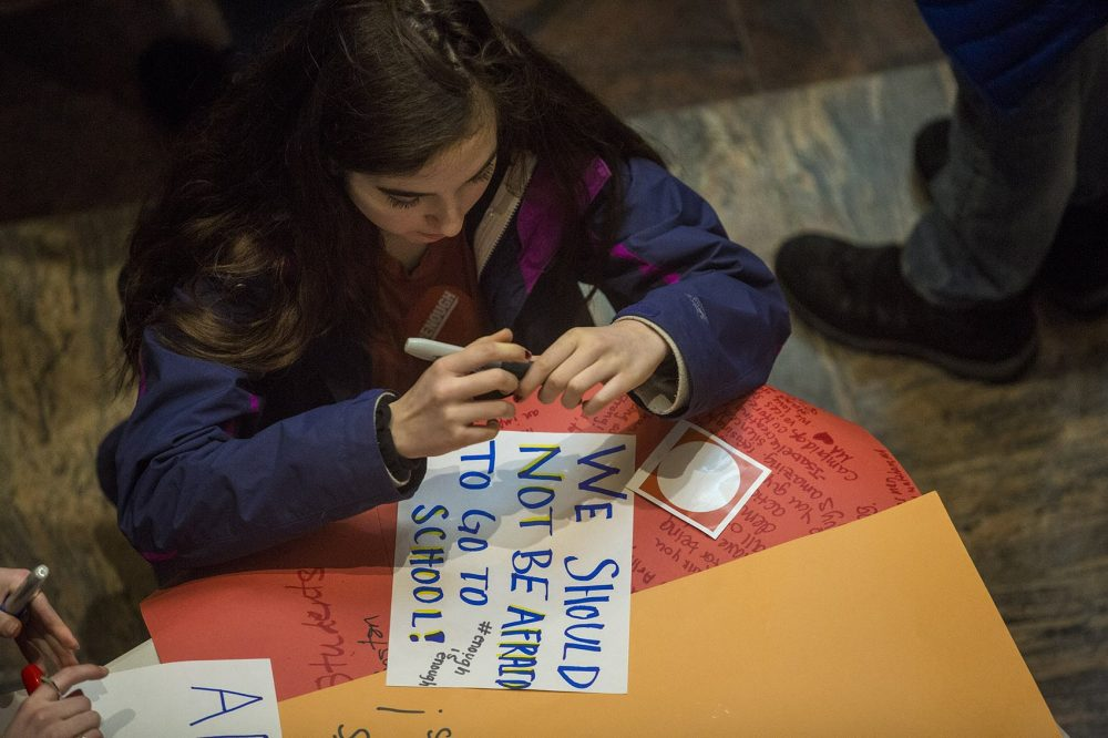 A student finishes creating a sign at a gathering at St. Paul's Cathedral before the march to the State House. (Jesse Costa/WBUR)
