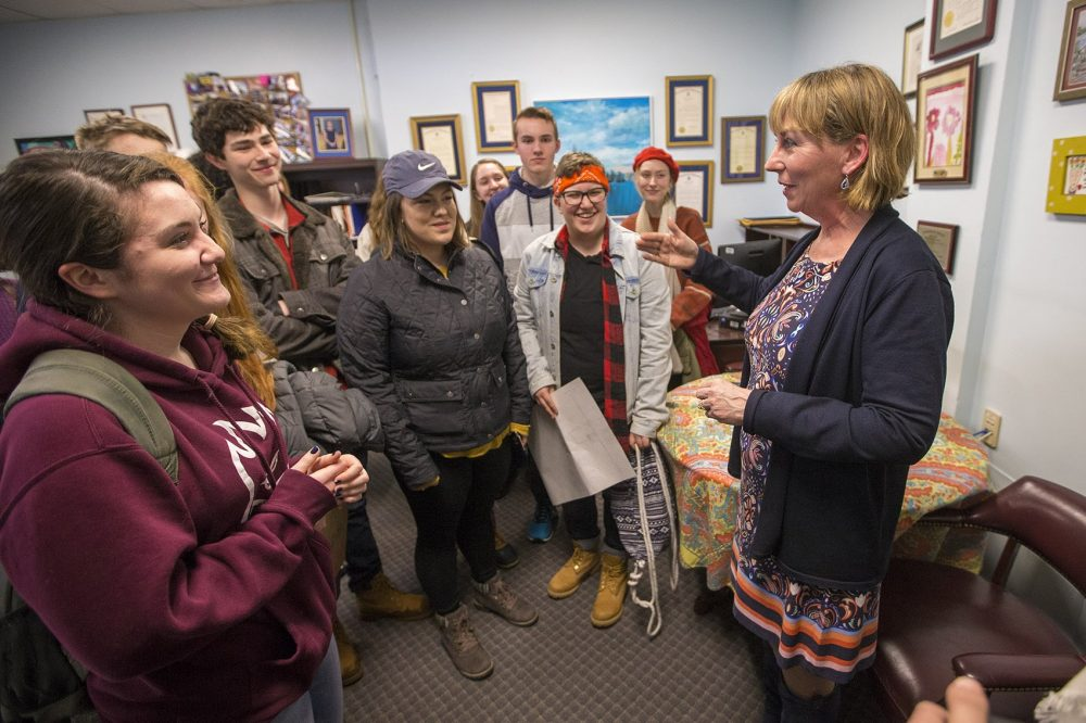 A group of Andover High School students speak with state Sen. Barbara L'Italien at her office in the State House. (Jesse Costa/WBUR)
